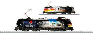 Trix Scala H0 - Märklin Scala H0 - Locomotiva elettrica della Mitsui Rail Capital Europe con fiancate a livrea asimmetrica per l'anniversario della caduta del Muro.